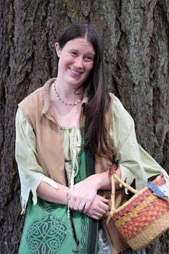 Riona in traditional Celtic attire posed by a tree